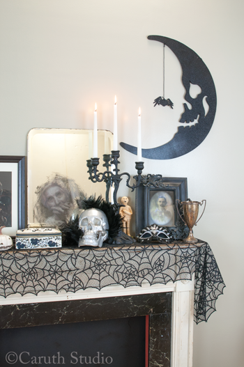 mantel with Halloween decoration and a scary moon silhouette above