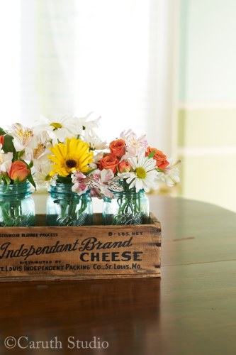 Flowers in mason jars inside vintage cheese box