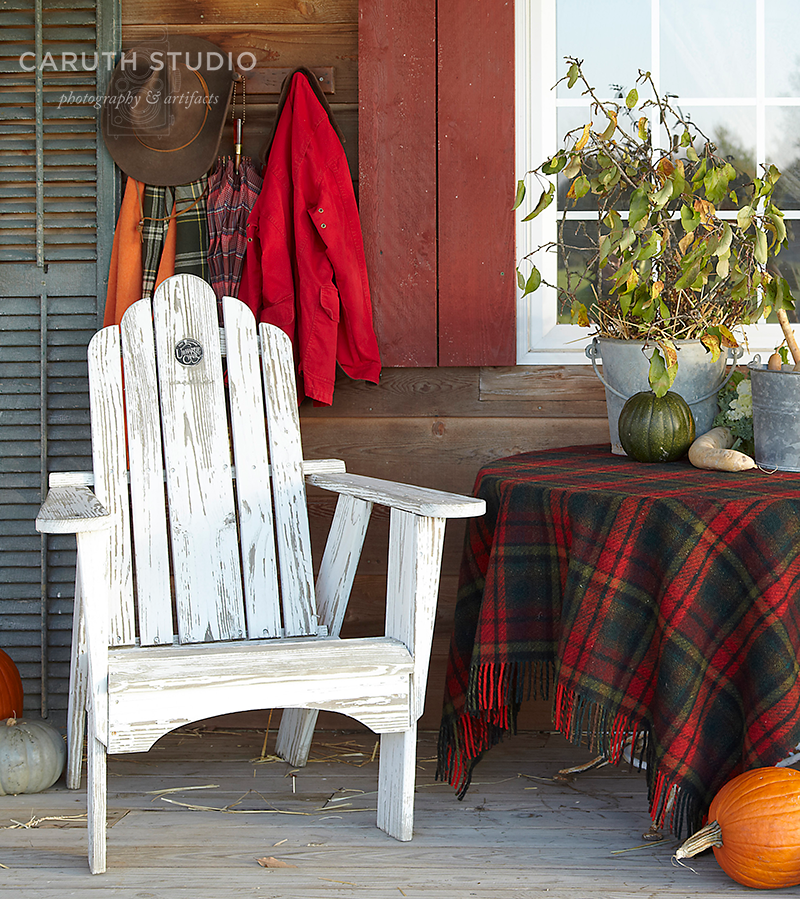 White Adirondack chair on porch with decorated table and various colored pumpkins
