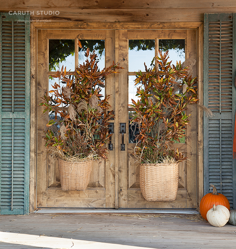 Baskets filled with dry botanicals on wooden french doors