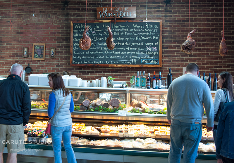 Huge cast of Wurst Deli meats with 4 shoppers in front of a large brick wall and chalk board menu
