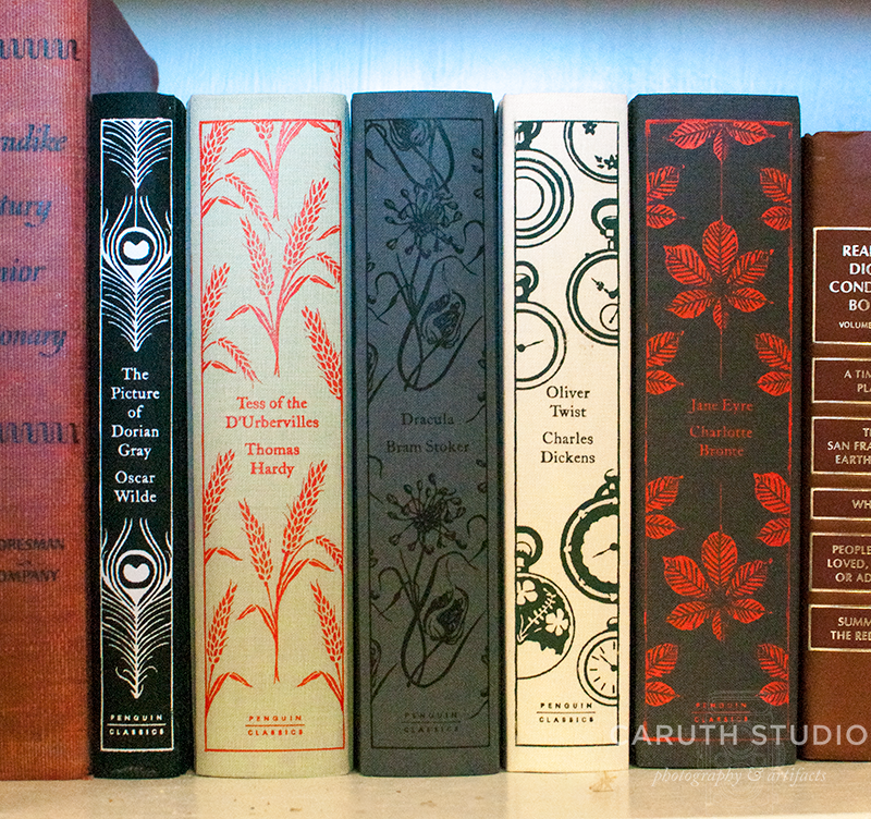Books on shelf with decorated spines in reds, blacks and whites.
