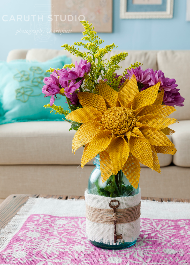 yellow burlap flowers among real pink flowers in vase