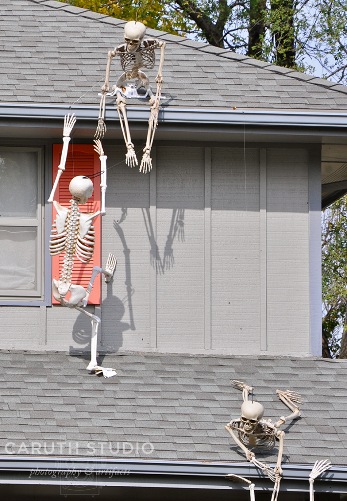 3 Skeletons climbing to the roof of a house