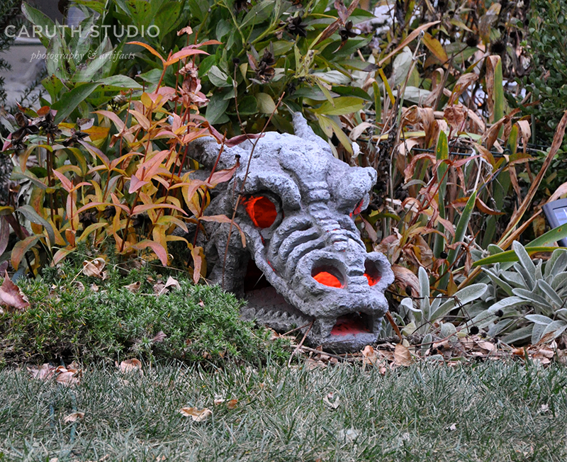 Glowing red dragon skull in flower bed