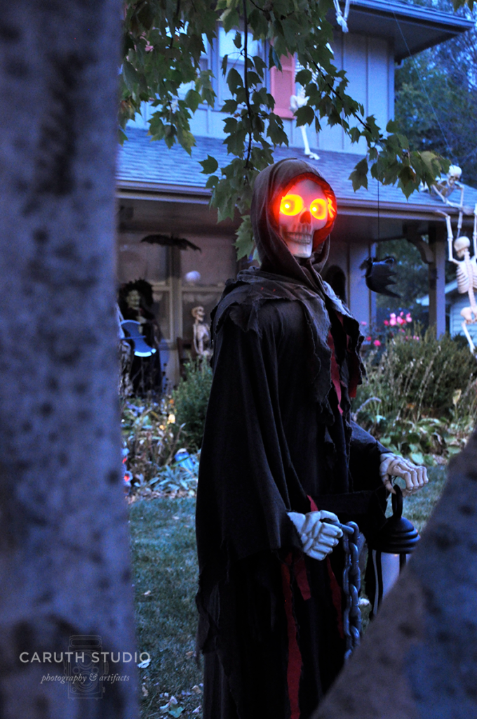 Grim reaper at night with lantern and chains and glowing red eyes