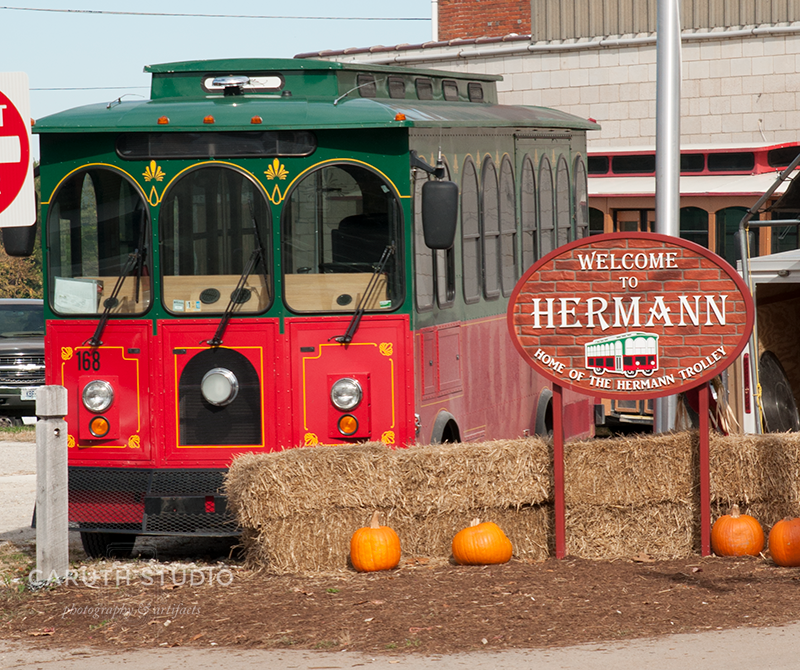 Hermann trolley of dark green and red next to hay bales and pumpkins