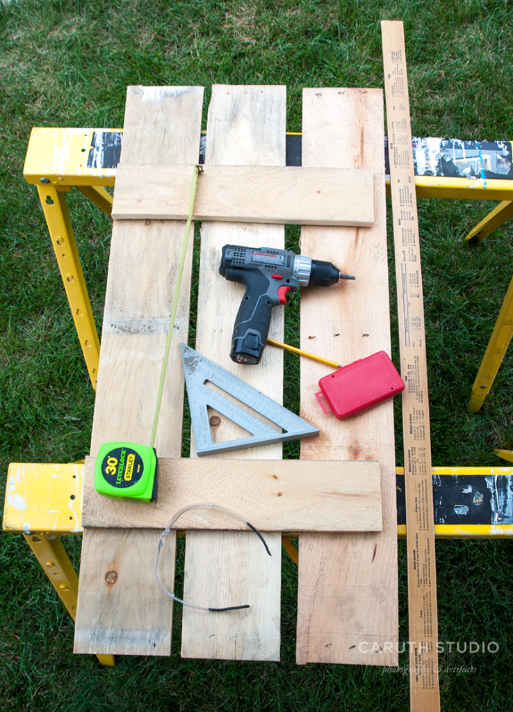 drill, measuring tape, triangle, pencil, ruler and wood laid out
