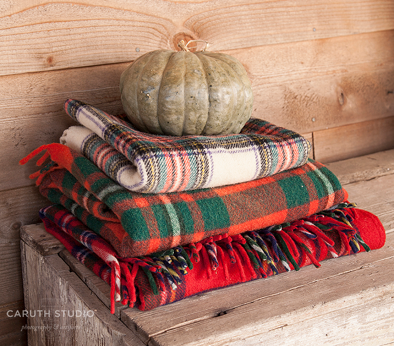 Pile of wool blankets in red, white and green with a pumpkin on top.