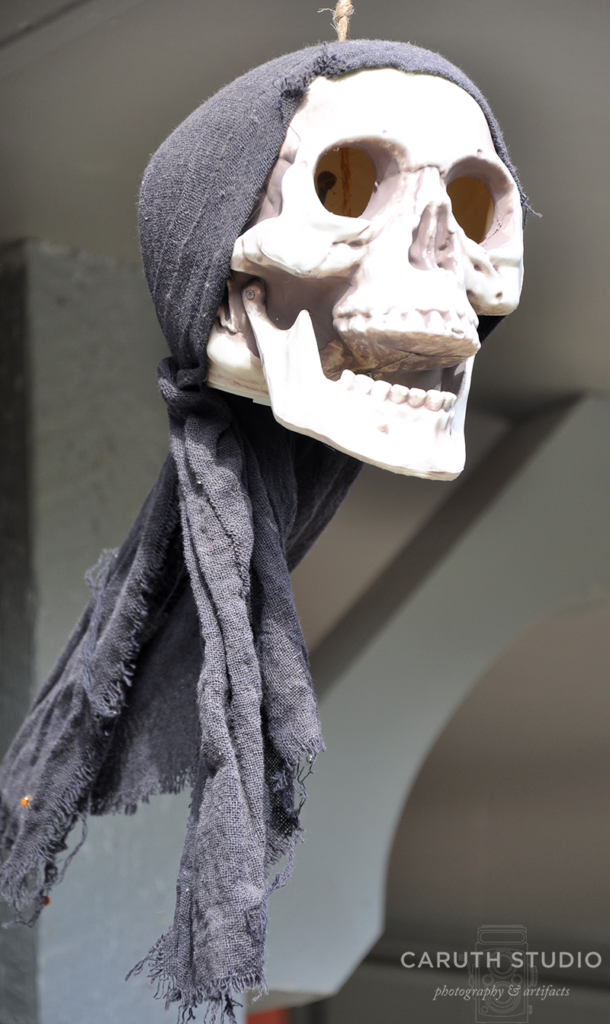 Pirate skull with black headband hanging from the house porch roof
