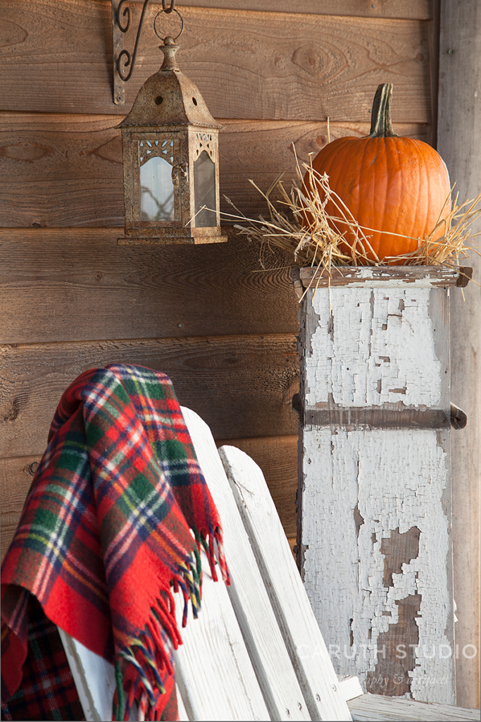 Pumpkin on white pillar with wheat, lantern, white deck chair and plaid wool blanket