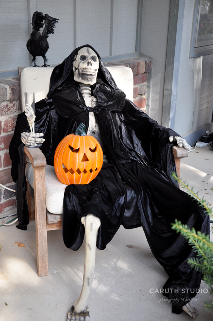 Seated skeleton in a black cloak, wine glass, and a jack o'lantern in his lap