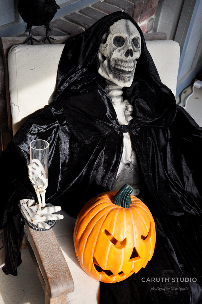 clost picture of the seated skeleton in a black cloak, wine glass, and a jack o'lantern in his lap