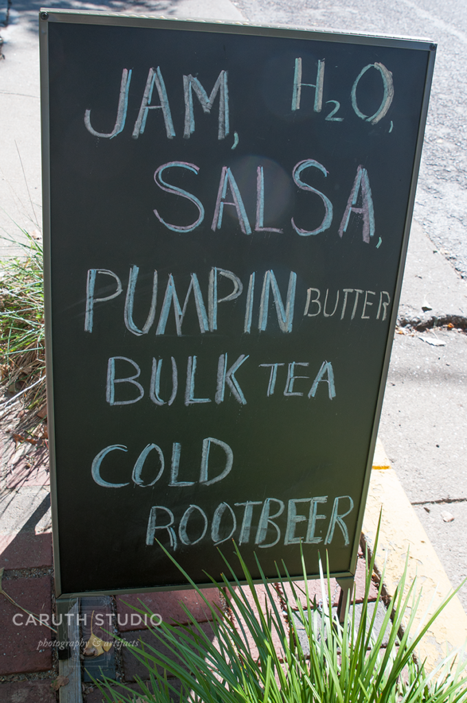 Shop sign listing Jam, water, salsa, pumpin [sic] butter, bulk tea, and cold rootbeer
