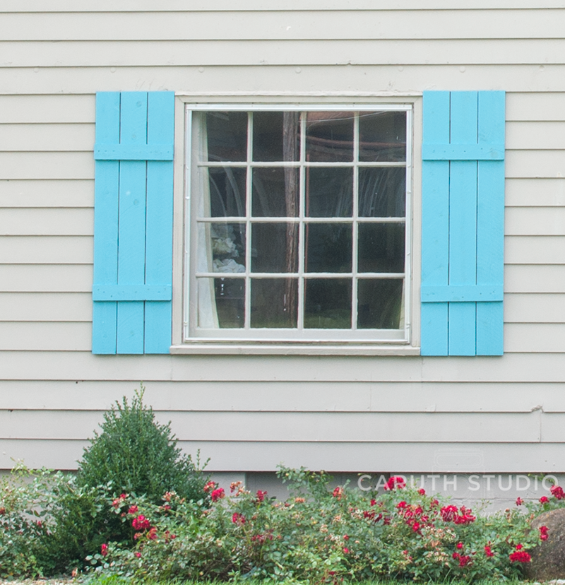 Teal Shutters hanging on either side of a window