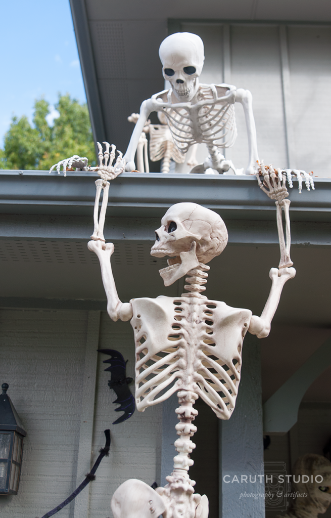 Skeletons trying to aid each other climbing the roof of a house