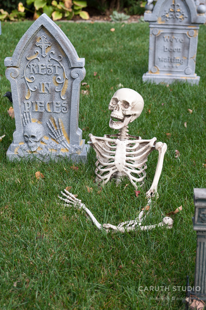 Skeleton in pieces raising from the ground in a grave yard