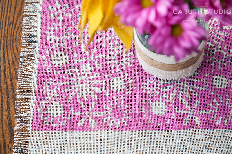 Stenciled pink burlap runner with white flower motif underneath a vase full of pink and yellow flowers