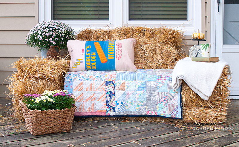Sofa made of straw bales covered in a quilt with a throw pillow
