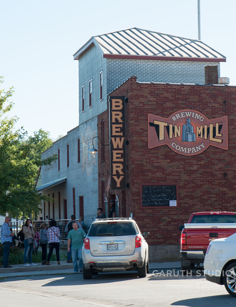 Tin Mill Brewery with a big Brewery sign in gold and black hanging on an old brick building
