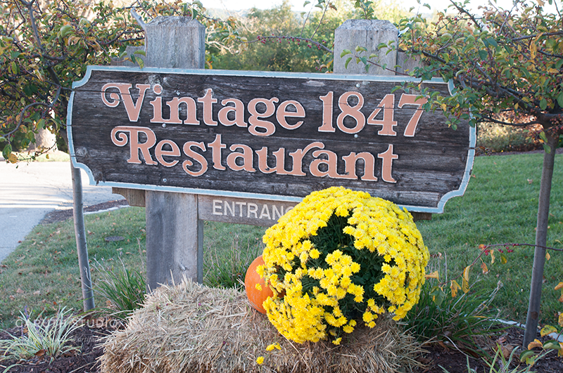 Vintage 1847 restaurant sign with flowering mums and pumpkin