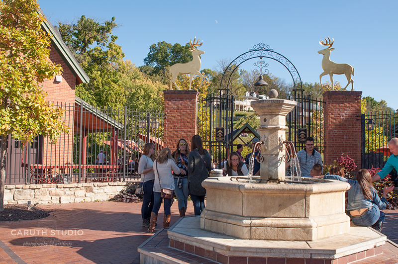 Winery entrance with a fountain which a dozen people are standing and sitting on and around