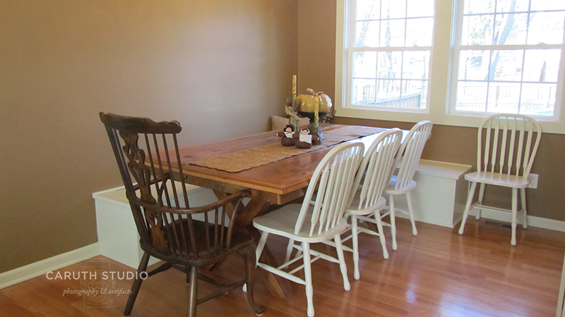 Dining room barnwood table surrounded by white and brown wood farm chairs