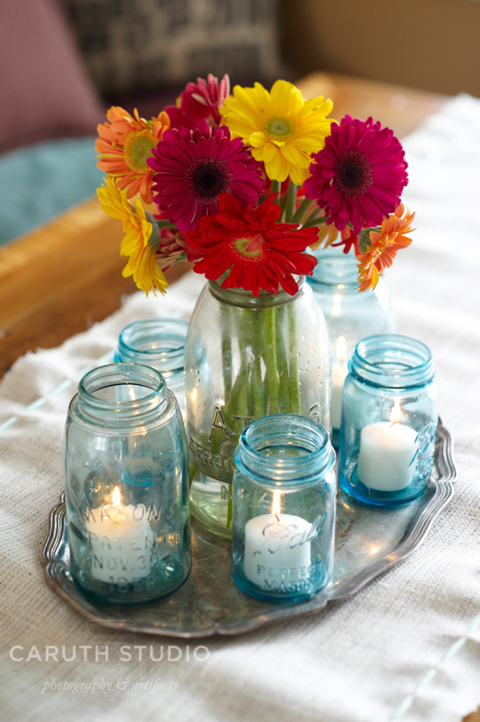 Mason jars with lit votives around a vase of yellow and red flowers