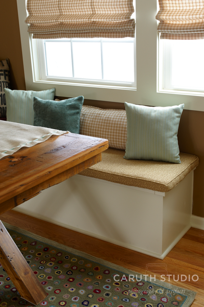 New banquette seating in beige and white with light blue accent pillows under a window
