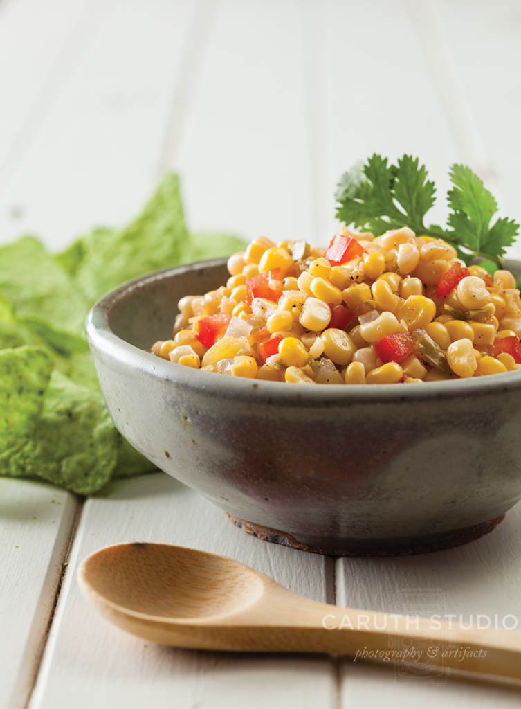 Corn salsa in gray bowl with lettuce and a wooden spoon