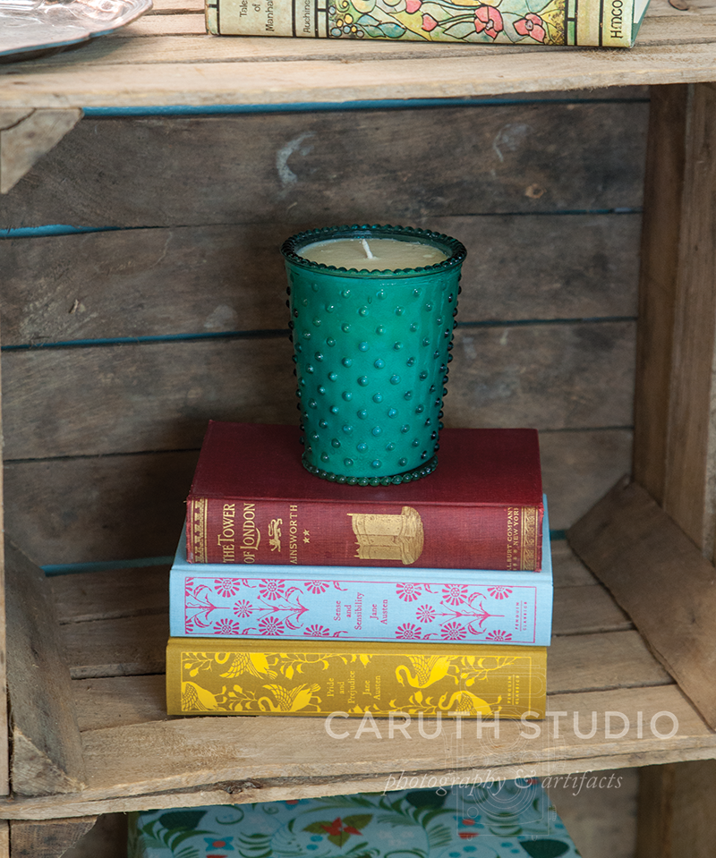 Crate nightstand with canvas bound books and teal candle
