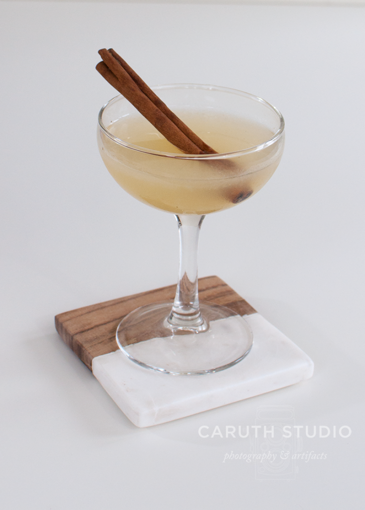 Modern English cocktail with cinnamon stick on marble and wood coaster