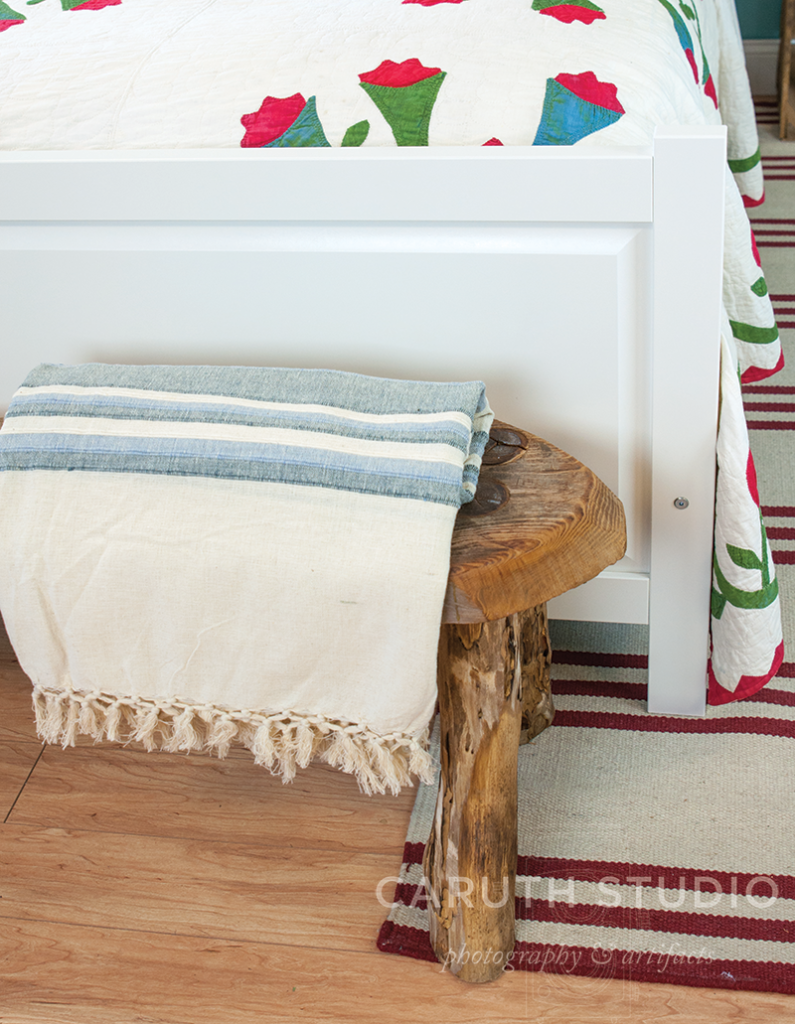 Rustic wooden bench with blue and cream throw