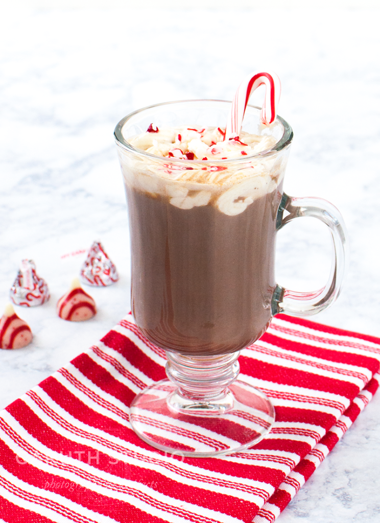 Spiked Cocoa in glass mug on candy-cane napkin with pepermint chocolate kisses chocolate in the background