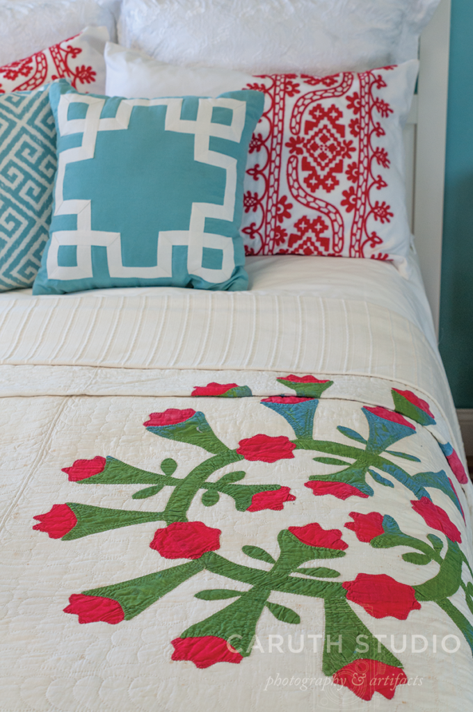 Vintage quilt with red flower pinwheel motif on white backing