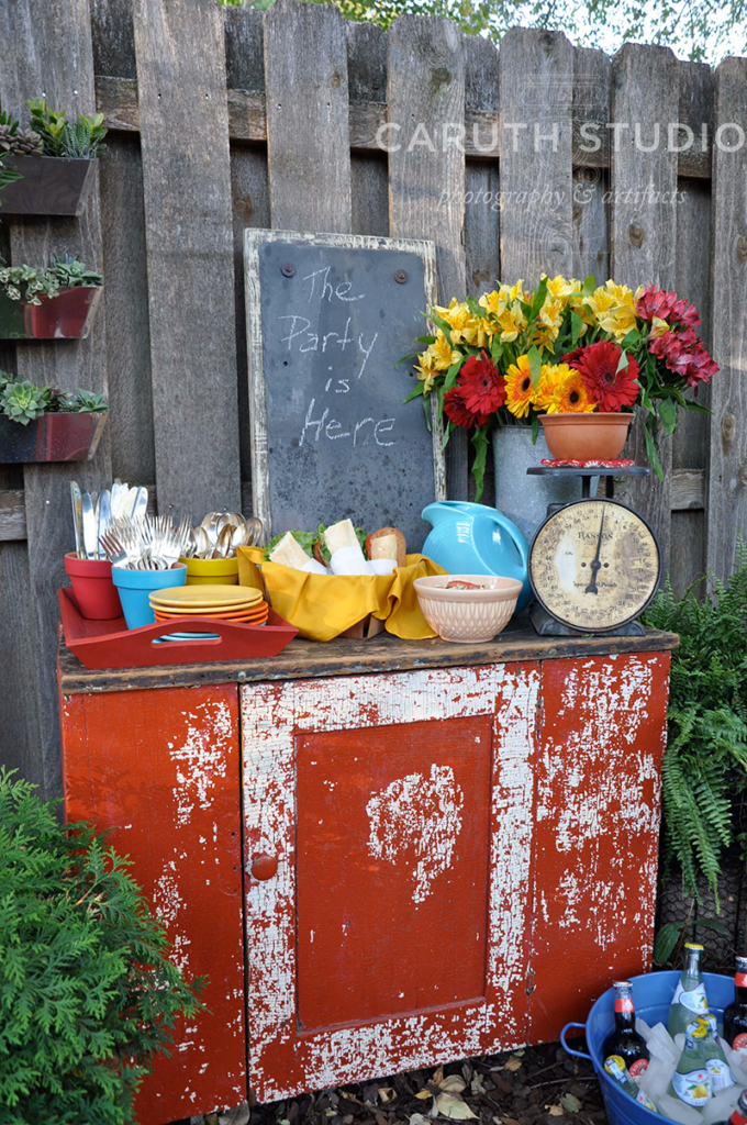 Buffet cupboard with fiesta ware and a scale with flowers