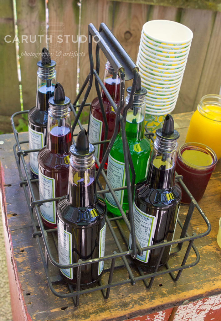 bottles of snowcone syrups in antique milk carrier