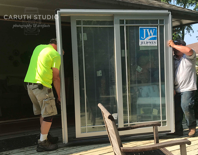 two men carrying patio door into place