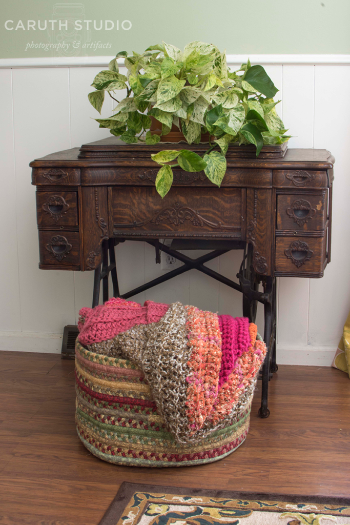 old wooden sewing machine with potted vine on top and basket full of crochet blankets below
