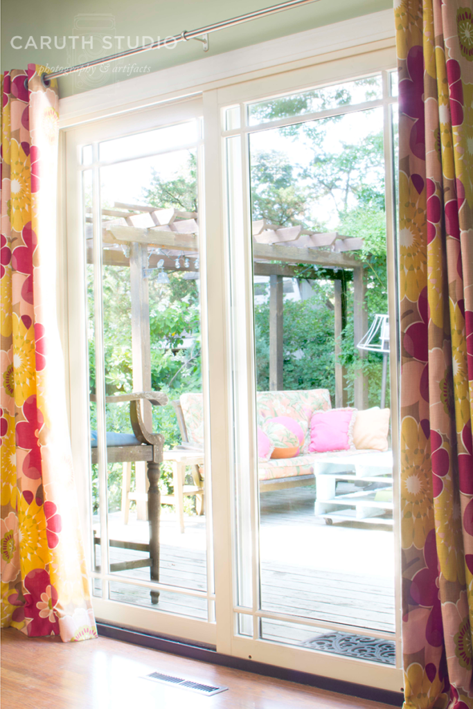 new patio door full of light flanked by warm curtains
