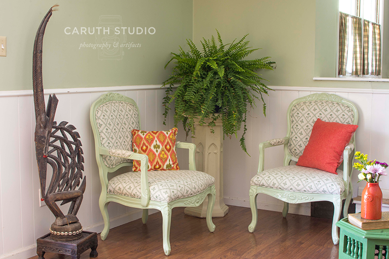 two chairs with pillows around a pedestaled fern
