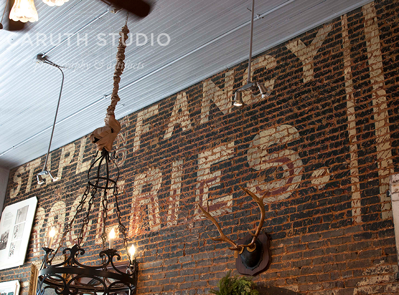 painted brick on the store interior that reads 'staple and fancy groceries'