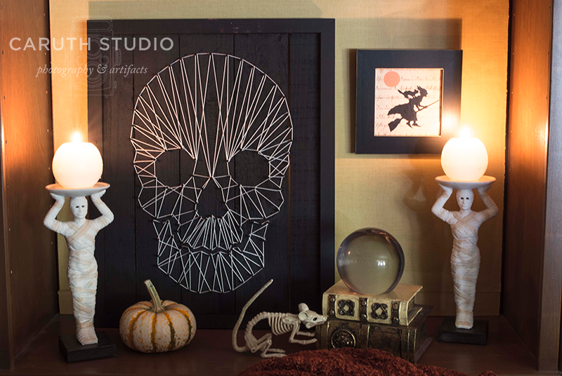 framed skull string art between two mummy lamps, behind a rat skeleton, glass ball and pumpkin