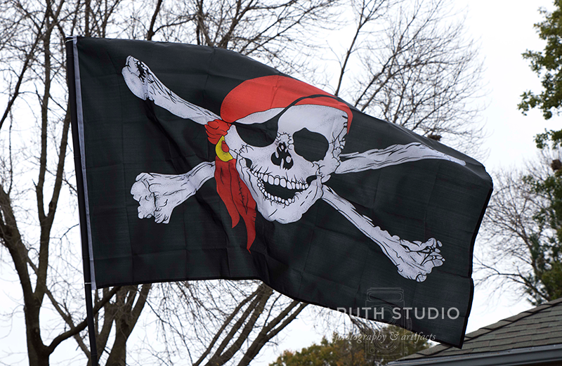 pirate flag with skull with eyepatch and red headscarf and crossbones flapping in the breezes