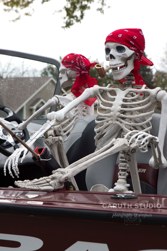 two skeletons on a boat both wearing read head scarves - one skeleton is driving the boat, the other is relaxing a fishing
