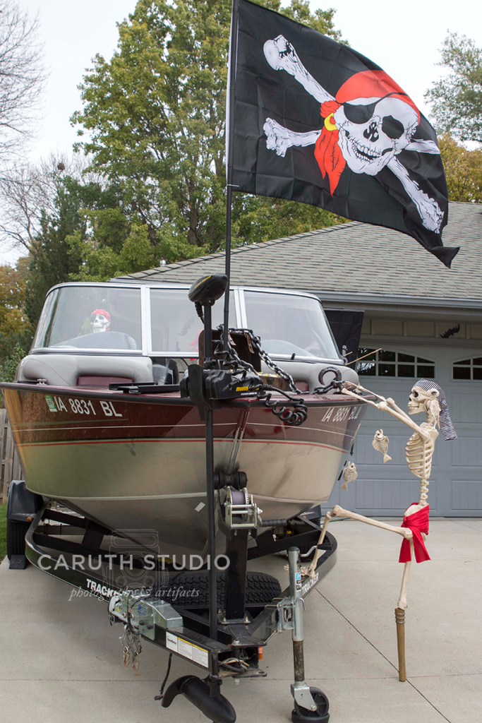skeleton pirate crew on the elevated boat in a suburban driveway decorated with pirate flag, skeleton fish, and a chest of booty