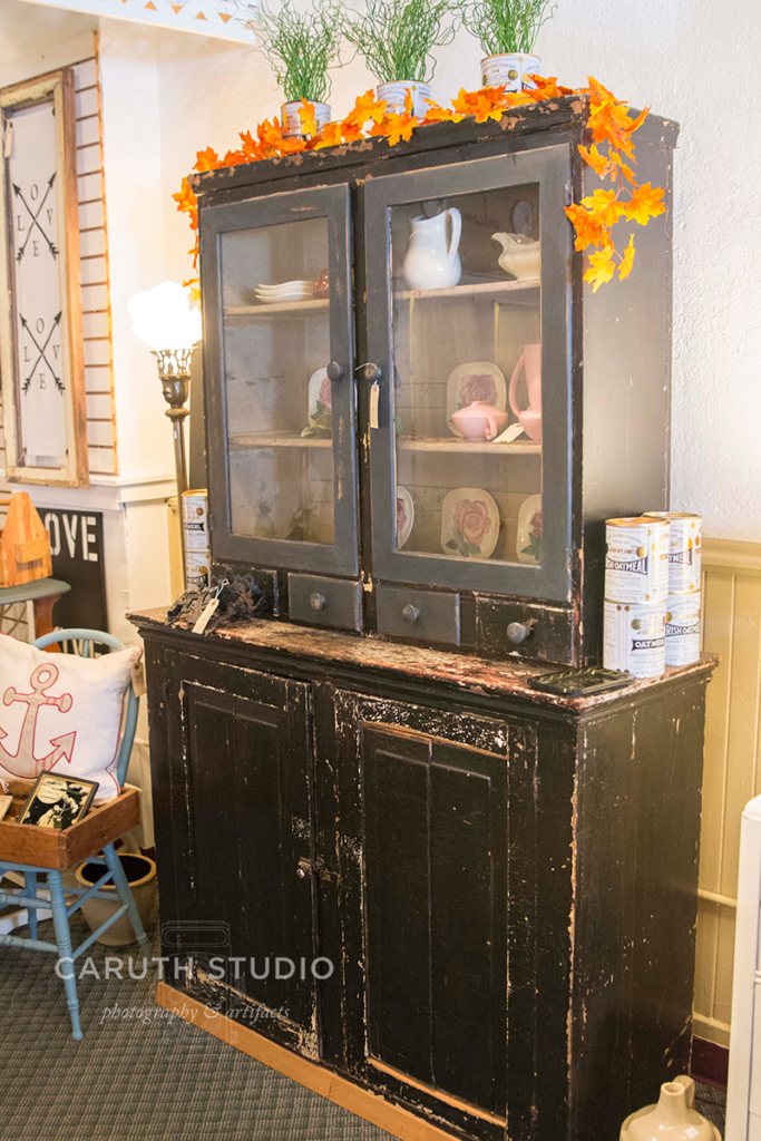 dark antique armoir filled with vintage dishes