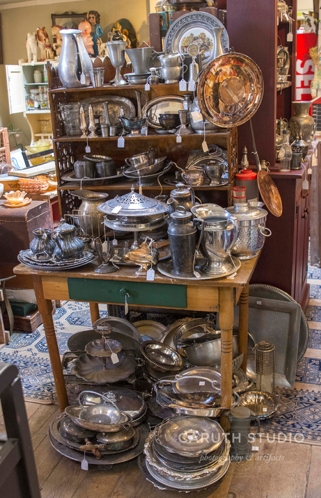 antique table piled high with silver, pots, pans, and glasses
