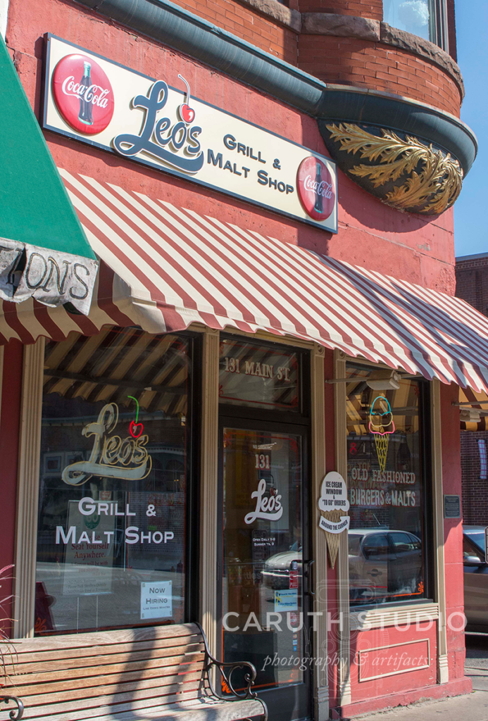 Leo's grill and malt shop storefront in red brick and a stripped red and white awning