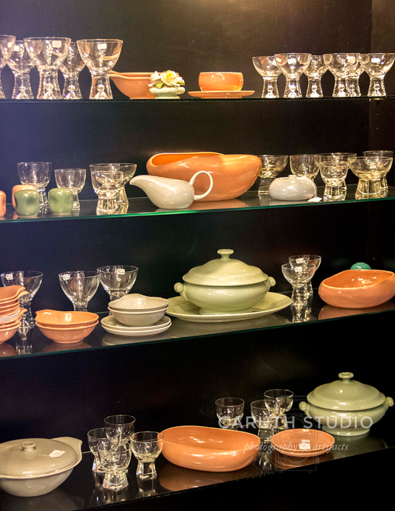 display of orange and green mid century dish ware in a black cabinet